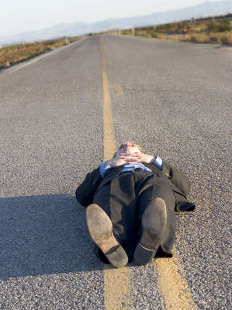 tenseness: Businessman in black suit is laying down in the middle of the road in the desert