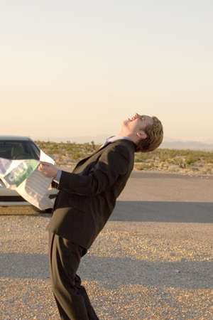 Businessman is in a frustrated pose as he holds his map in his hands outside his parked car in the middle of the desert Reklamní fotografie