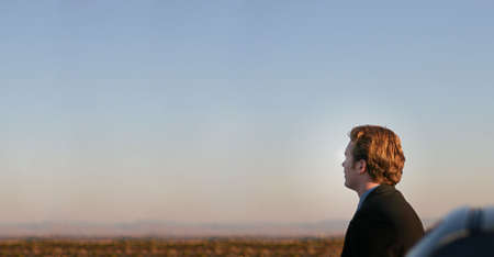 Businessman in black suit and brown hair stands next to his car outside and looks toward the desert horizon