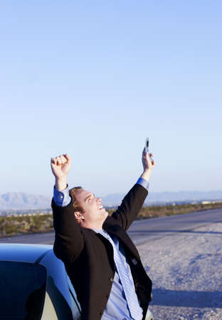inventiveness: Businessman in black suit holds cell phone in one hand as he raises both his arms in victory as he stands next to his parked car in the middle of the desert