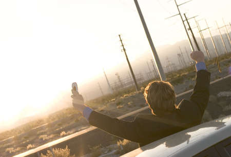 Businessman in black suit holds up cell phone in hand as he raises both his arms in victory as he stands outside his parked car in the middle of the desert as the sun is going down