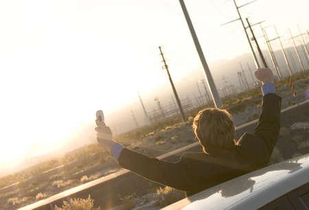 spunk: Empresario en traje negro sostiene tel�fono celular en la mano como �l plantea tanto en sus brazos la victoria ya que est� fuera de su autom�vil estacionado en medio del desierto mientras el sol va abajo