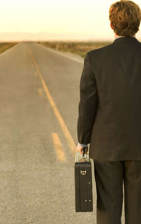 Businessman dressed in black suit is holding briefcase in the middle of the desert road, which leads to success