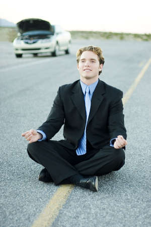 Businessman in black suit and blue shirt sits in the middle of the road and meditates as his car is parked and has its hood up off to the side