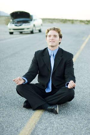Zakenman in zwart pak en blauwe shirt zit in het midden van de weg en meditates als zijn auto wordt geparkeerd en heeft zijn kap omhoog naar de kant