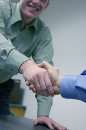 firmness: Businesmen dressed in green and blue shake hands over a conference table
