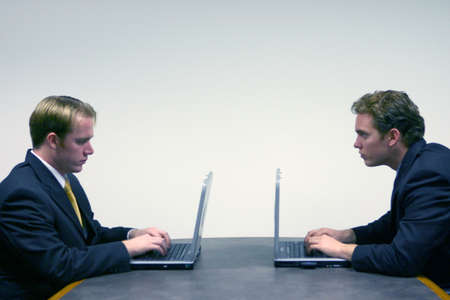 strategizing: Business men in black suits face each other as they sit down around a conference table typing on their laptops Stock Photo