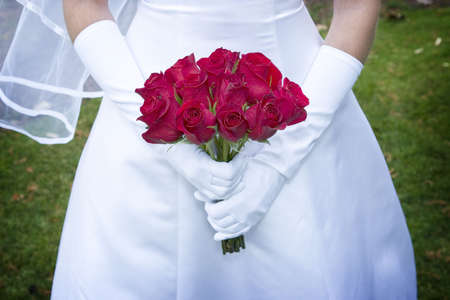 spousal: bride is in wedding dress as she holds onto her red roses Stock Photo