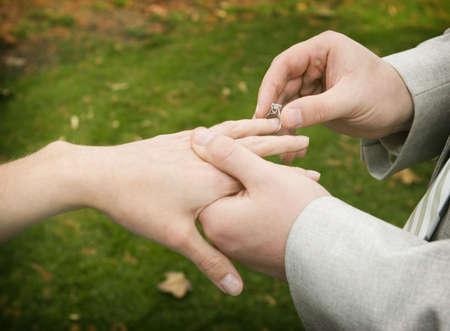 Groom slips on wedding ring onto bride's finger Stock Photo - 460167