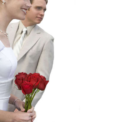 spousal: Young bride and groom are smiling as they look in the same direction and the bride is holding roses