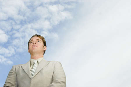 hitched: Groom looks up with blue sky and clouds in the background Stock Photo