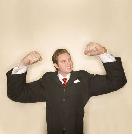 captivating: Business man in black suit, red tie, and white shirt is flexing is arms in a pose of strength whose arms are incredibly exaggerated