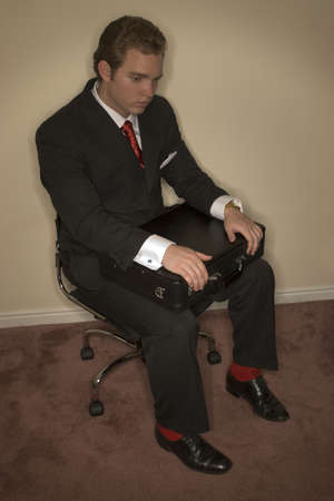 Business man in black suit, red tie, red socks, and white shirt is holding is briefcase in a emotionless position photo