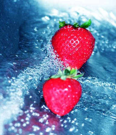 fortifying: Rushing water with fresh, red strawberries Stock Photo