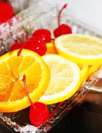 fortifying: Cherries, lemons, oranges, and strawberries in a plastic container