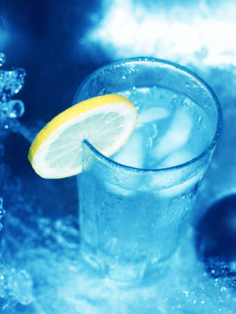fortifying: Glass of water with lemon slice around its edge surrounded by rushing, blue water Stock Photo