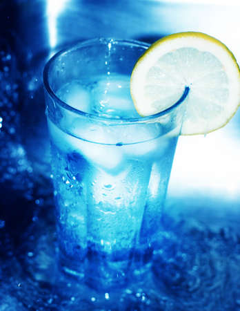 fortifying: Glass of cool water has lemon slice around its edge as it is surrounded by rushing water Stock Photo