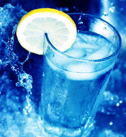 fortifying: Glass of cool water with lemon slice around its edge, surrounded by rushing blue water Stock Photo