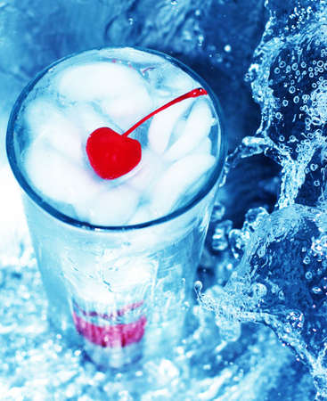 fortifying: Red cherry in refreshing glass of water, next to tidal wave of water Stock Photo