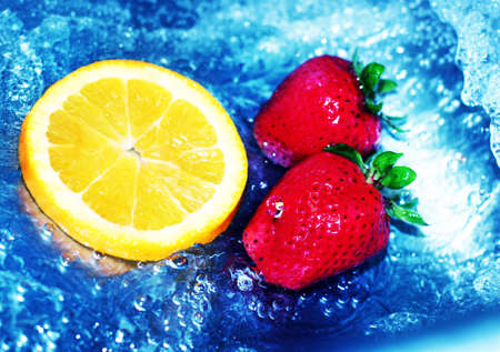 fortifying: Red strawberries floating next to orange slice in cool, refreshing water Stock Photo