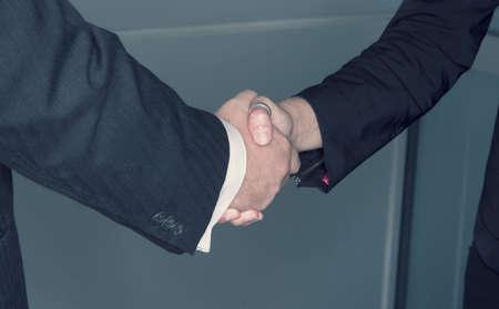firmeza: El hombre y la mujer de negocios sacudaren delante de un fondo de cristal Foto de archivo