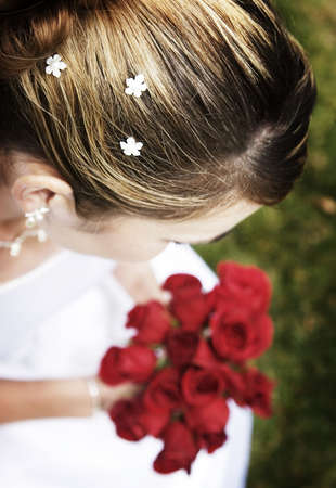 Woman dressed in wedding dress is holding roses on the green grass Stock Photo