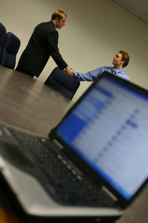 Two men in background shake hands while laptop screen is displaying information on the conference table