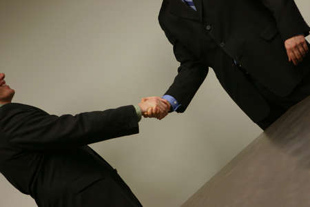 Two white business males in green and blue shirts handshake Stok Fotoğraf