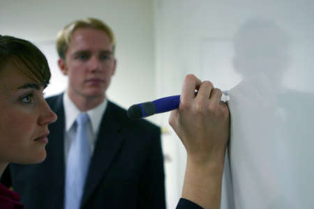 strategizing: Business woman writes on white board as man dressed in blue tie looks on
