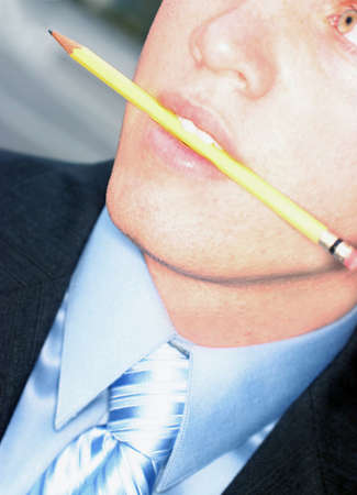 Business man in blue shirt is biting down on yellow pencil as he looks away