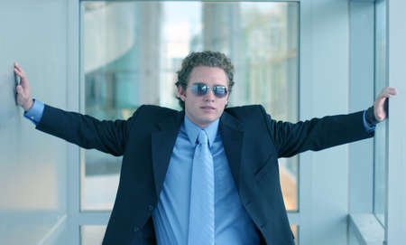 taking charge: Business man wearing blue shirt and blue tie is wearing sunglasses as he stretches arms out touching both walls of the hallway Stock Photo
