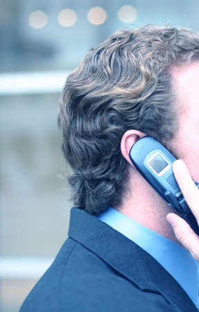 Business man holds up cell phone to his ear in front of business building photo