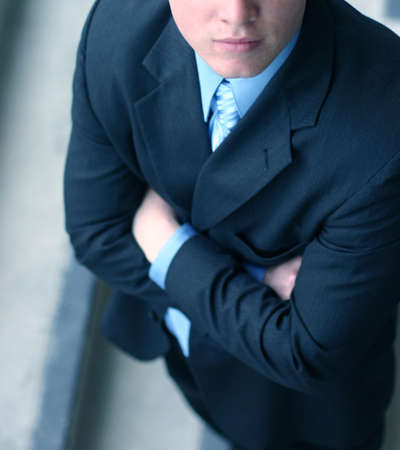 folding arms: Business man in darker suit, blue shirt, and blue tie is folding his arms