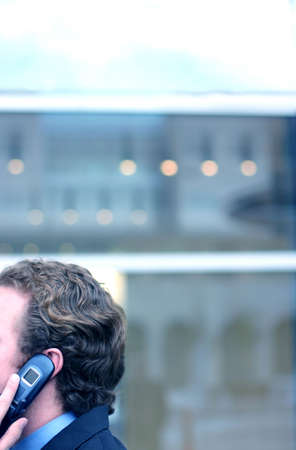 no rush: Business man holds onto his cell phone in front of business building