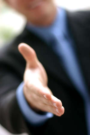 firmness: Business man in blue shirt and tie extends hand in a warm, open gesture Stock Photo