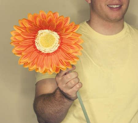 hope indoors luck: Man in yellow shirt holds orange, yellow flower