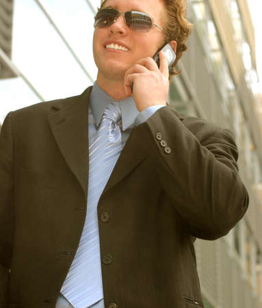 taking charge: Business man in blue shirt and blue tie is wearing sunglasses as he talks on his cell phone Stock Photo