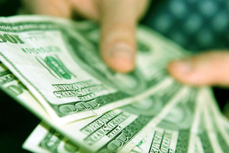 Businessman holding onto his money and one hundred dollar bills Stock Photo - 590192