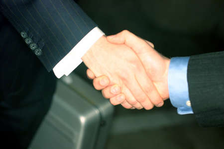 southern european descent: Businessmen give a handshake with a briefcase in the background