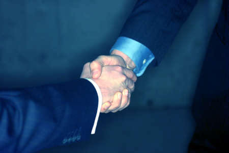 southern european descent: two businessmen give a handshake with their suits on Stock Photo