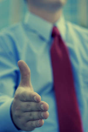 Businessman giving a handshake greeting with a red tie and blue shirt Stock Photo - 590197