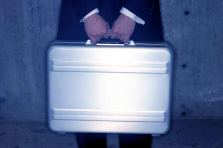 Businessman holds his briefcase in front of his body for security