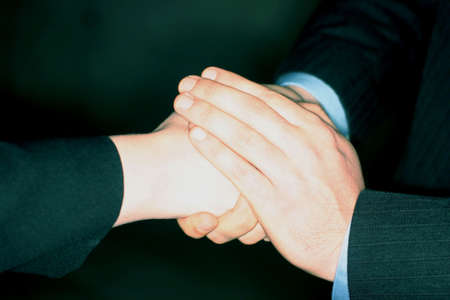 two persons only: Businessman gives a warm handshake to a businesswoman