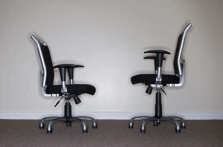 taller: Two business chairs where one chair is looking at the other when which is taller
