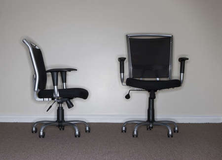 taller: One business chair is facing and looking at the taller, more confident business chair, which is the boss
