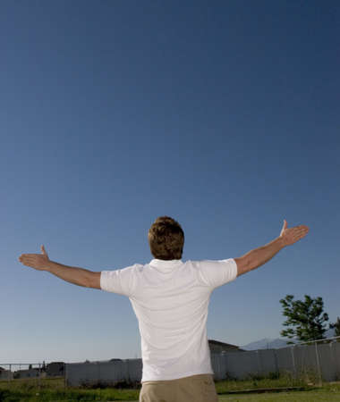 Young man raises his arms and looks up in the blue sky in his backyard Banco de Imagens