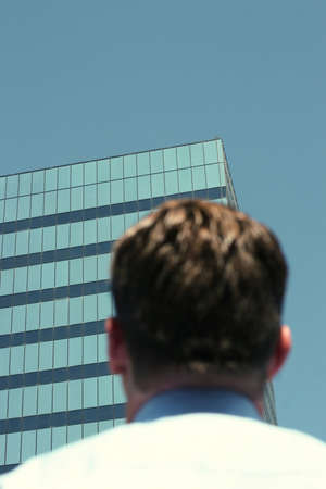 Businessman looking up at the business building in a blue sky