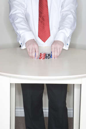 Man standing at a table holding some gambling chips in his hands Stock Photo - 854473