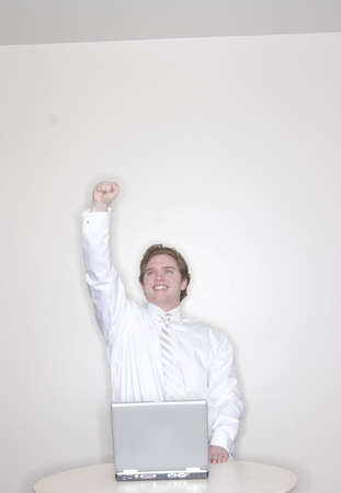 Businessman raises his arm in a sign of success while standing in his office with his laptop photo