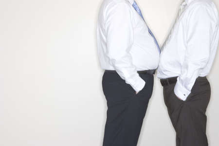 Two businessmen confront each other and face off by standing close to each other in the office Stock Photo
